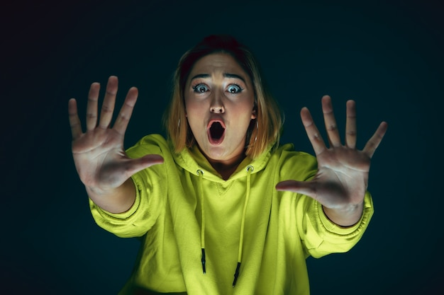 Close up portrait of young crazy scared and shocked caucasian woman isolated on dark background.