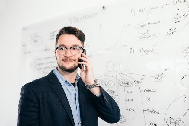Ritratto del primo piano di giovane uomo dai capelli scuri in piedi vicino alla lavagna e parlando al telefono in ufficio. indossa camicia blu, giacca scura, occhiali. sorride di lato.