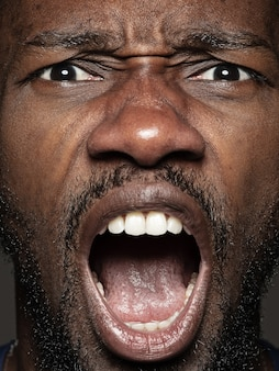 Close up ritratto di giovane ed emotivo uomo afro-americano. modello maschile con pelle ben tenuta ed espressione facciale luminosa. concetto di emozioni umane. urlando.