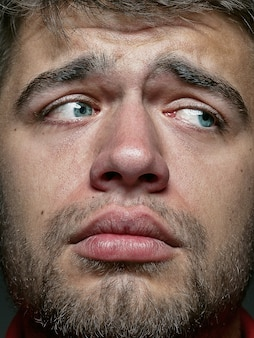 Close up portrait of young and emotional caucasian man. highly detail photoshot of male model with well-kept skin and bright facial expression. concept of human emotions. looks sad and upset.