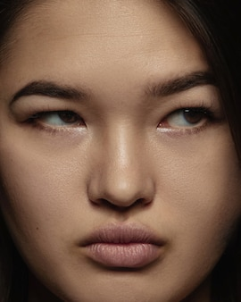 Close up portrait of young and emotional chinese woman. highly detail photoshot of female model with well-kept skin and bright facial expression. concept of human emotions. serious, looking at side.