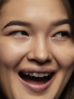 Close up portrait of young and emotional chinese woman. highly detail photoshot of female model with well-kept skin and bright facial expression. concept of human emotions. smiling, happy.