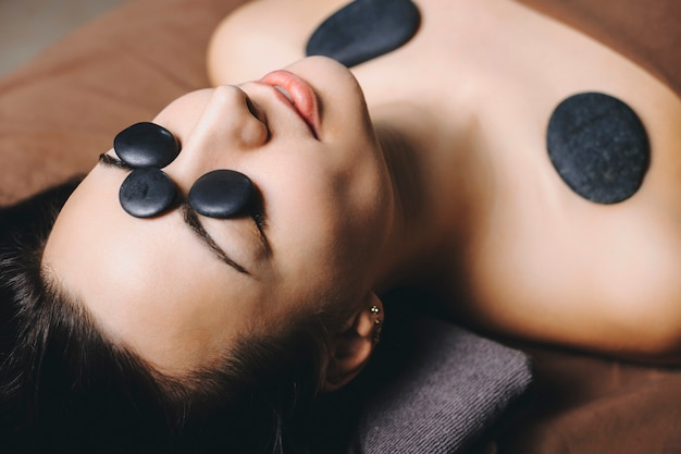 Close up portrait of a young european female having hot stone therapy on her face and shoulders while leaning on a spa bed with closed eyes in a wellness center.