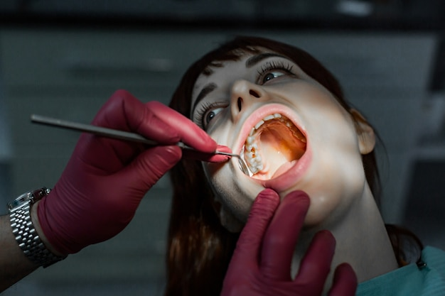 Close up portrait of young female patient with open mouth having professional dental treatment, and hands of doctor wearing red rubber gloves, holding dental mirror