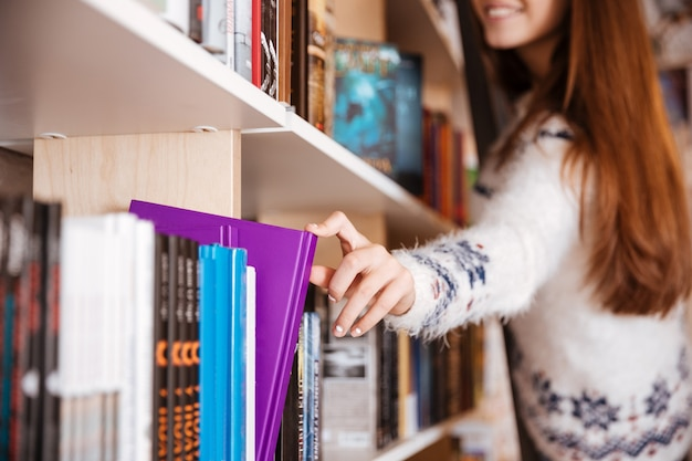 Close up portrait of a young female student taking book from book shelf