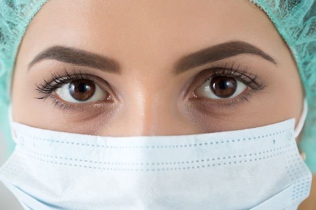 Close up portrait of young female surgeon doctor or intern wearing protective mask and hat. healthcare, medical education, emergency medical service, surgery or veterinary concept