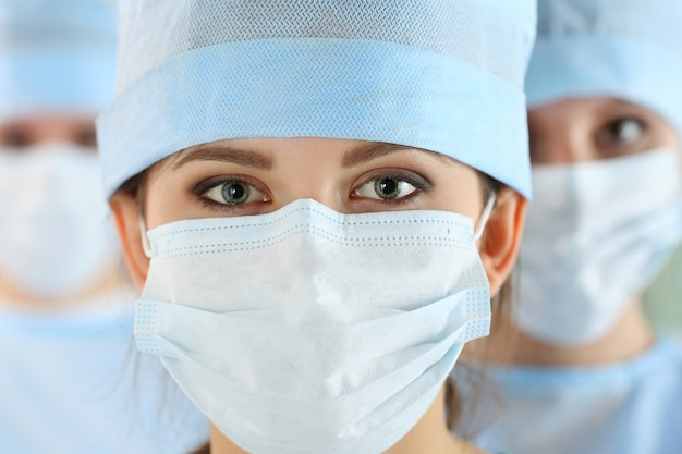Close-up portrait of young female surgeon doctor surrounded by her team. group of surgeon in operation theatre. healthcare, medical education, emergency medical service and surgery concept