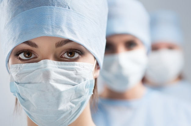Close-up portrait of young female surgeon doctor surrounded by her team