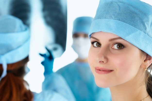 Close up portrait of young female surgeon doctor surrounded by her team