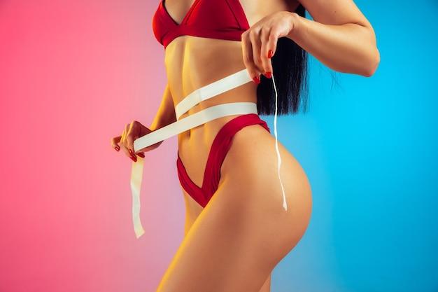 Chiuda sul ritratto di giovane donna caucasica adatta e sportiva in costume da bagno rosso alla moda sul gradiente