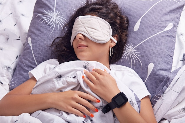 Close up portrait of young girl with eye mask sleeping under blanket, having hard work and wants to relax, lying in bed on pillow, having dark hair, dressed white t shirt, has black clock on hand.