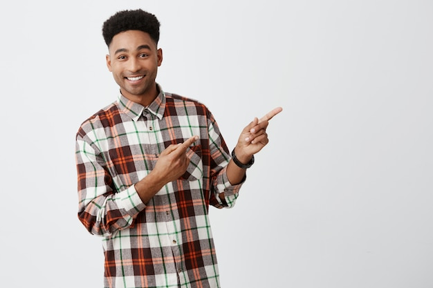 Close up portrait of young good-looking dark-skinned man with stylish dark afro hair in checkered shirt smiling with teeth, pointing aside won white wall with happy and joyful expression