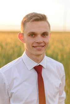 Close-up portrait of a young groom. man smiles in a wheat field