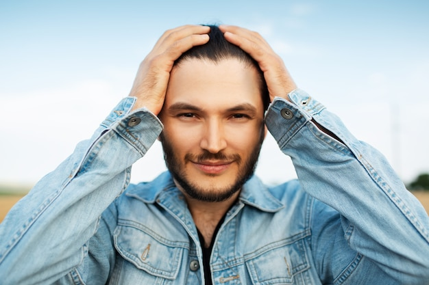 Close-up portrait of young guy in denim jacket holding hands on head.