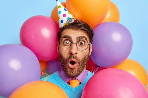 Close up portrait of young guy surrounded by party balloons posing