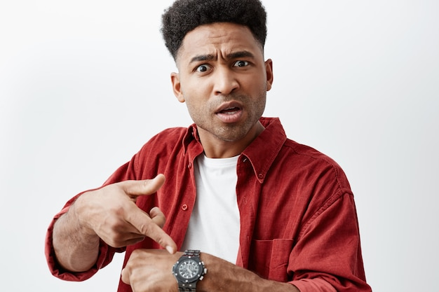 Close up portrait of young handsome black-skinned man with afro hairstyle in casual white t-shirt under red shirt pointing at hand watch with unsatisfied expression, after his friend being late.