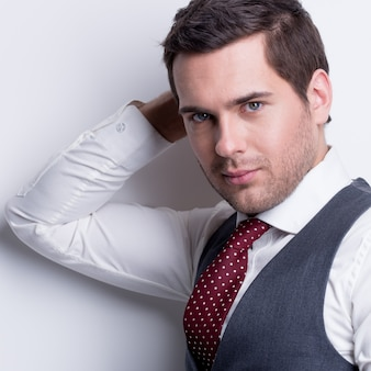 Close-up portrait of a young handsome man in suit posing