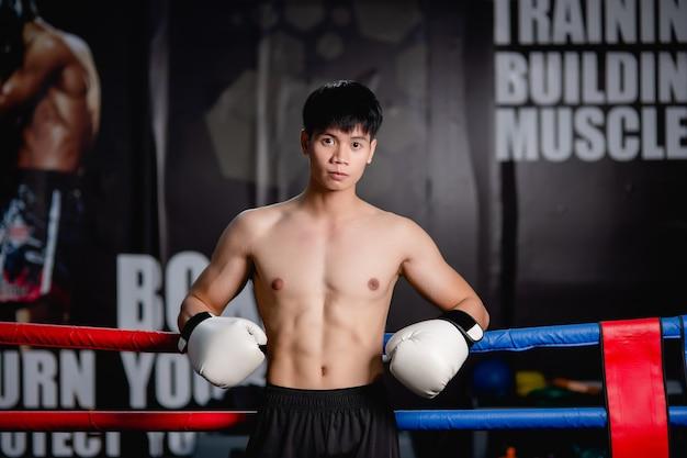 Primo piano, ritratto giovane uomo bello in guanti da boxe bianchi posa in piedi su tela in palestra fitness, lezione di boxe allenamento uomo sano,,