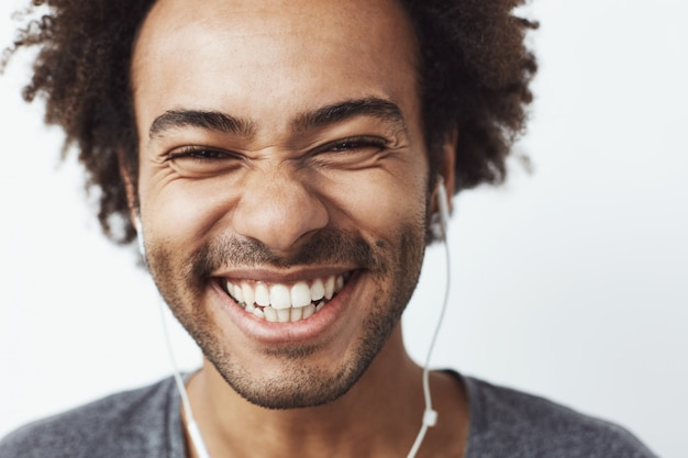 Close up portrait of young happy african man smiling listening to upbeat streaming music laughing. youth concept.