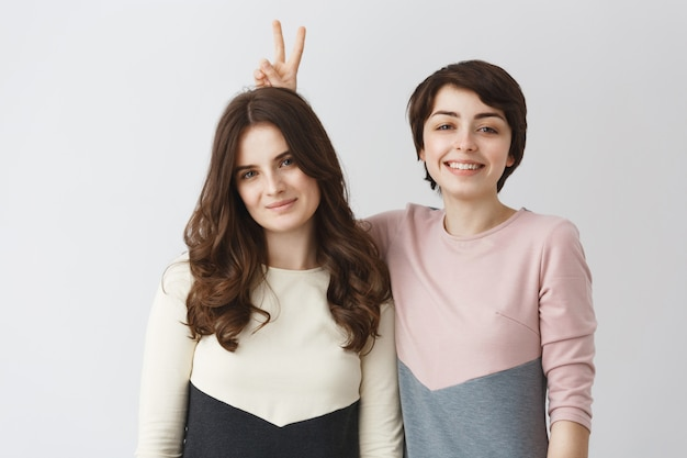 Close up portrait of young happy lesbian pair with dark hair in matching clothes smiling, having fun, posing for shoot in photo booth.