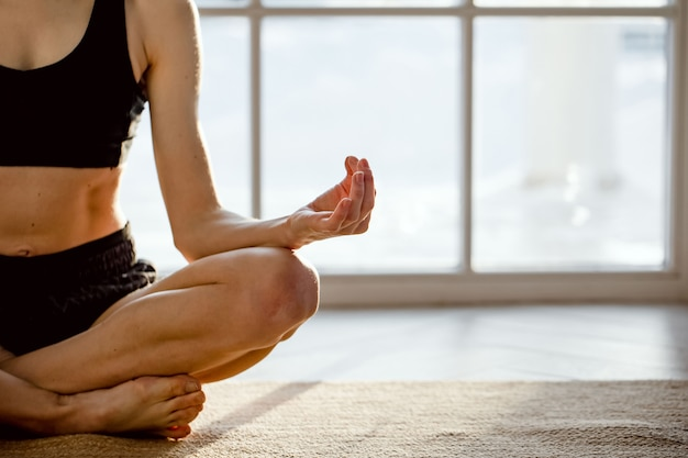 Close up portrait of young healthy woman sitting in lotus position and meditating.