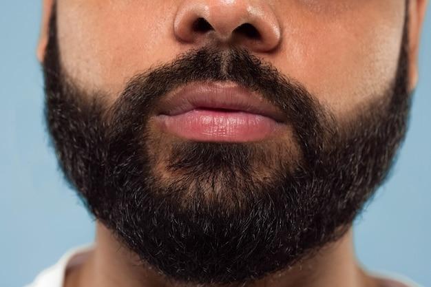 Close up ritratto del volto di giovane uomo indù con barba e labbra su sfondo blu. sembra calmo. emozioni umane, espressione facciale, concetto di pubblicità. spazio negativo.