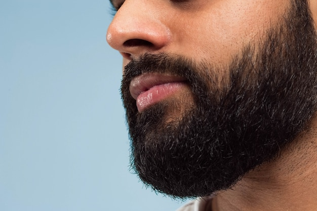 Close up portrait of young hindoo man's face with beard and lips on blue space