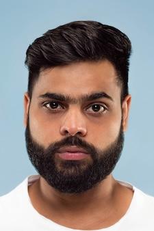 Chiuda sul ritratto di giovane uomo indù con la barba in camicia bianca isolata sulla parete blu. emozioni umane, espressione facciale, concetto di annuncio. spazio negativo. in piedi e con aria calma.