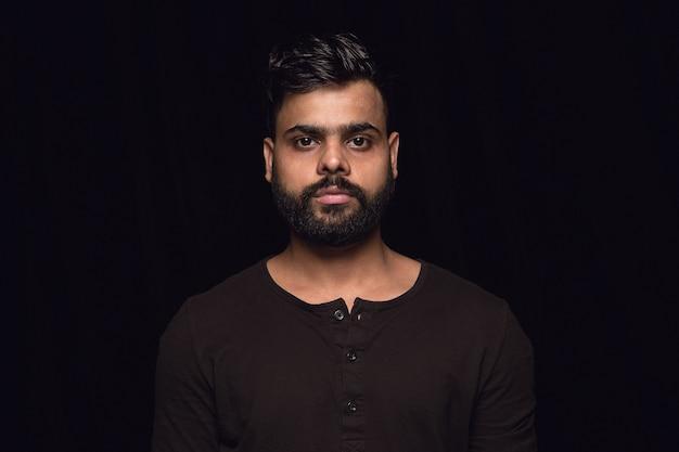 Close up ritratto di giovane uomo indù isolato. in piedi e sembra serio. espressione facciale, natura umana e concetto di emozioni.