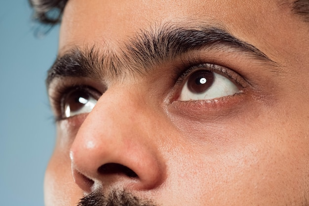 Close up portrait of young indian man's face with brown eyes looking up or at side. human emotions, facial expression. looking dreaming or hopeful.