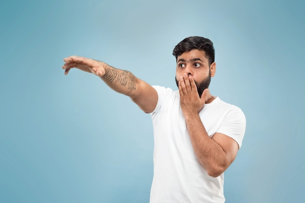 Close up portrait of young indian man in white shirt. pointing up being shocked and astonished.