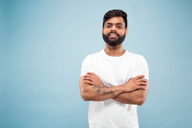 Close up portrait of young indian man in white shirt.  posing, standing and smiling, looks calm.