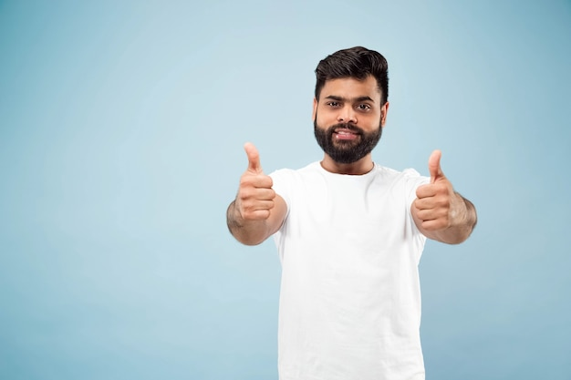 Close up portrait of young indian man in white shirt.  showing the sign of ok, nice, great. smiling.