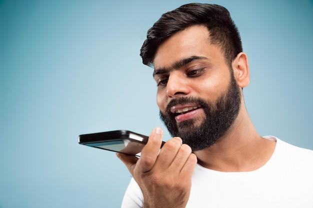 Vicino ritratto di giovane uomo indiano in camicia bianca. parlando al cellulare, registrando un messaggio vocale.