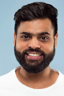 Close up portrait of young indian man with beard in white shirt isolated.  standing and smiling.