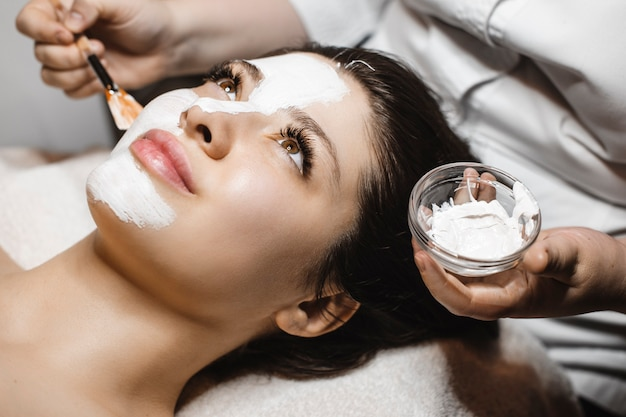 Close up portrait of a young lovely female having a anti acne mask in wellness spa center.