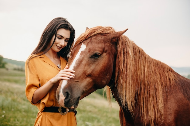 Close up portrait of a young lovely girl embracing a horse on a field. young caucasian woman smiling touching a horse while traveling.