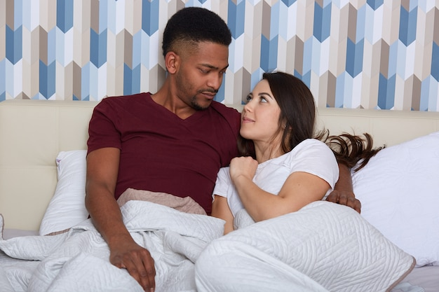 Close up portrait of young male and female lying in white bed togethe, wearing pajamas. romantic couple in love looking at each other, enjoying to spend time together. relationship abd people concept.