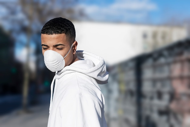 Close up portrait of young male wearing protective facial mask against transmissible infectious diseases and as protection against the flu or coronavirus in public place.