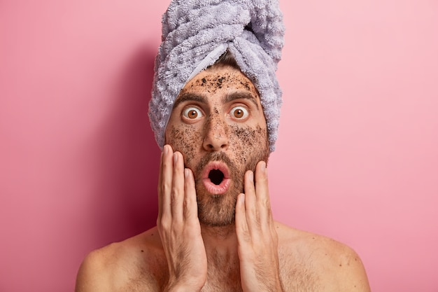 Close up portrait of young man cleans face with scrub, stares with bugged eyes and opened mouth, forgets about cosmetic cream, wears towel, has naked body
