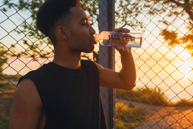 Close-up portrait of young man doing sports in morning, drinking water on basketball court on sunrise