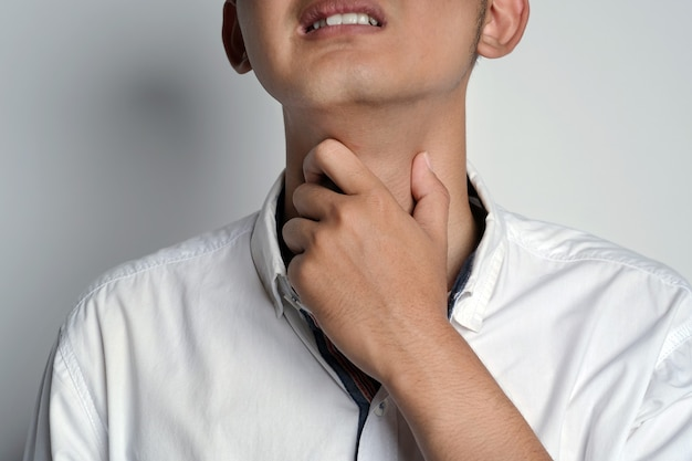 Close up portrait of young man having sore throat and touching his neck using his hands