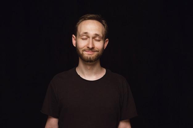 Close up ritratto di giovane uomo isolato su uno spazio nero. pensare e sorridere