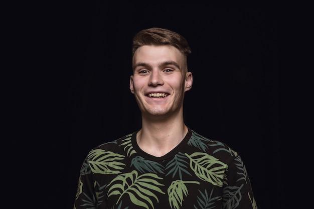 Close up ritratto di giovane uomo isolato su nero di sfondo per studio. photoshot di vere emozioni del modello maschile. sorridere, sentirsi felici. espressione facciale, concetto di emozioni umane pure e chiare.