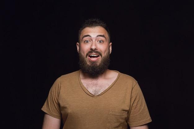 Close up ritratto di giovane uomo isolato su nero di sfondo per studio. photoshot di vere emozioni del modello maschile. meraviglioso, emozionante e stupito. espressione facciale, concetto di emozioni umane.