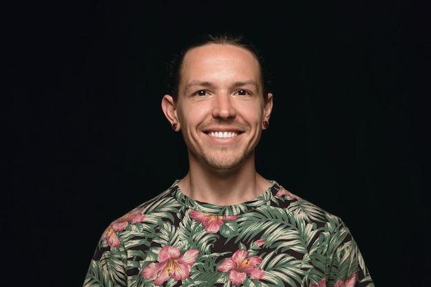 Close up ritratto di giovane uomo isolato su nero di sfondo per studio. sorridere, sentirsi felice.