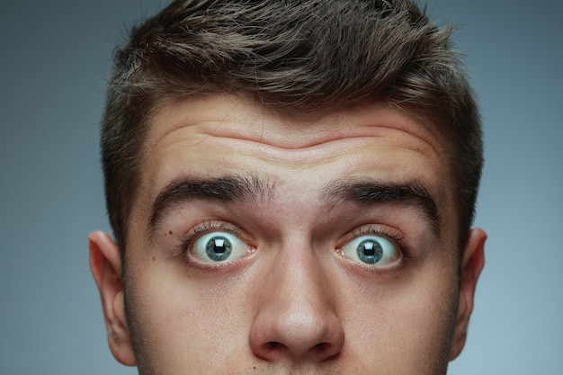 Close-up portrait of young man isolated on grey studio background. caucasian male model's face and blue eyes. concept of men's health and beauty, self-care, body and skin care. looks wondered.