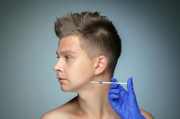 Close-up portrait of young man isolated on grey studio wall. filling surgery procedure, lips and cheekbones.