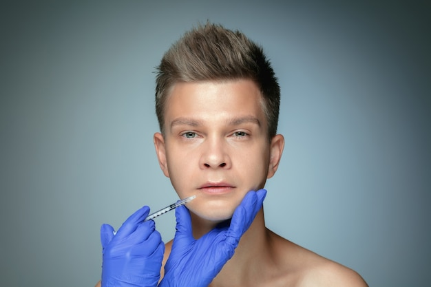 Close-up portrait of young man isolated on grey studio wall in filling surgery procedure