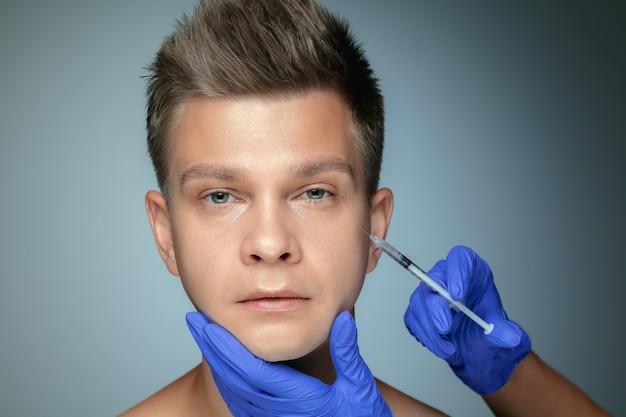 Ritratto del primo piano di giovane uomo isolato sul muro grigio. procedura chirurgica di riempimento. concetto di salute e bellezza maschile, cosmetologia, cura di sé, cura del corpo e della pelle. anti età.
